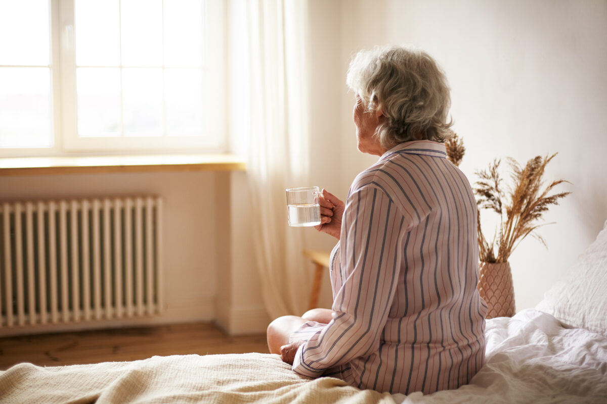 woman-with-gray-hair-holding-mug-recovering-from-covid-elderly-retired-female-taking-medicine-with-water-sitting-bedroom.jpg